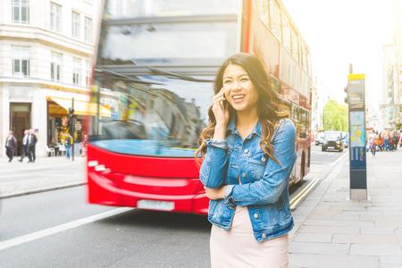 Asiatische Frau in London am Telefon. Schönes asiatisches Mädchen, das auf dem Bürgersteig geht, roter Doppeldeckerbus im Hintergrund. Reise- und Tourismuskonzepte