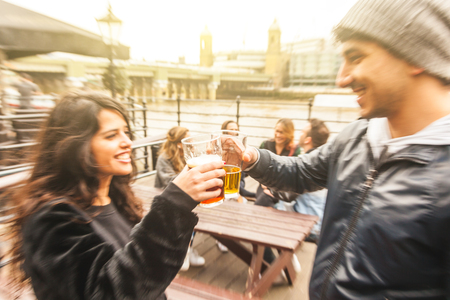 Happy friends couple drinking beer and toasting at outdoor pub brewery in London - Man and woman together with other people enjoying time together - Friendship happiness and lifestyle Zdjęcie Seryjne