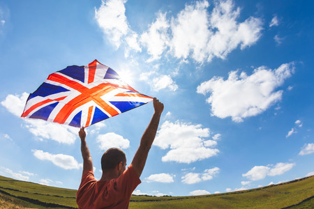 Man flying UK flag in the countryside - Union Jack flag with sunlight and cloudy sky on background - Actuality topic of brexit