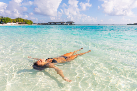 Beautiful woman relax afloat at tropical resort in Maldives islands - Woman wearing biking floating on crystalline water at seaside on a sunny day - Summer vacations and travel