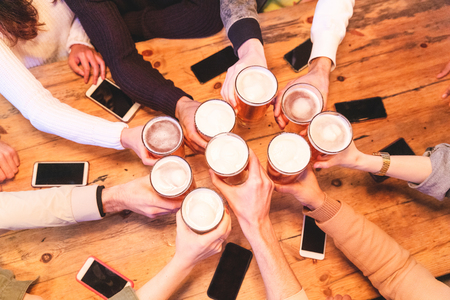 Friends drinking and toasting beer at pub brewery - Group of people cheering with pint of beer over wooden table with smartphones, top view, close up on hands - Friendship and lifestyle in London 写真素材