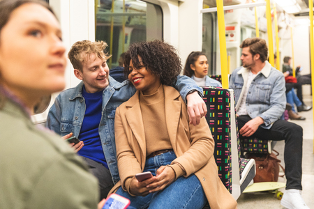 Multiracial couple travelling by tube together - White man and black woman together in subway train in London - Travel, love and commuting in millennials life