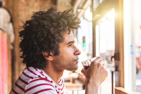 Thoughtful mixed race man drinking soda at cafe bar - Young man with afro style hair looking out of the window with a serious expression - Lifestyle image with summer tone and filter