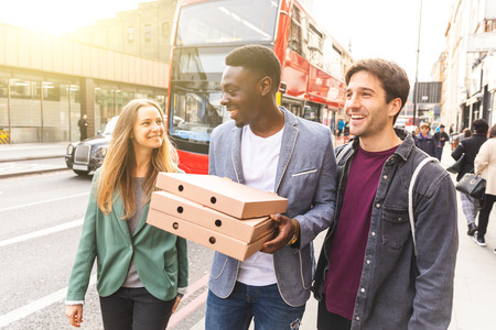 Happy friends with takeaway pizza in London - Multiracial group of best friends enjoying time together in the city and heading home with tasty food - Lifestyle and happiness, millennials culture Zdjęcie Seryjne
