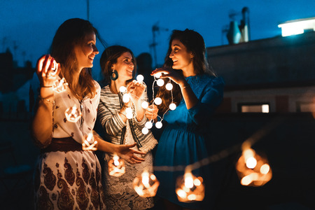 Happy women having fun at rooftop party with lights at night - Three beautiful women wearing summer clothes talking and dancing - Lifestyle and friendship in Barcelona