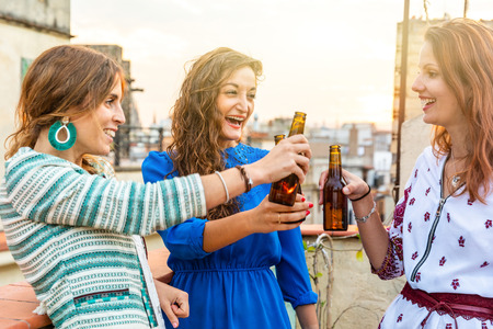 Happy women enjoying a beer on a rooftop in Barcelona - Three girls drinking a beer and having fun during a party at sunset on a rooftop with Gothic quarter on background in Barcelona Zdjęcie Seryjne