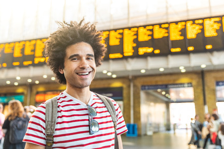 Happy man portrait at train station in London - Mixed race young man with curly hair looking at camera and smiling, waiting for train - Backpacker travel and lifestyle Archivio Fotografico