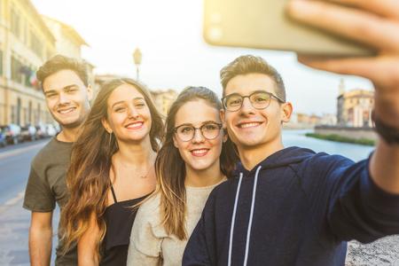Amici adolescenti che si fanno un selfie insieme in città dopo la scuola - Concetti di stile di vita e amicizia con un gruppo di ragazzi e ragazze che si divertono e si divertono insieme.