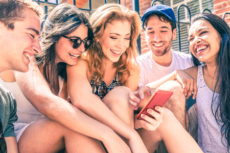 Happy multiracial friends having fun with a smartphone - Millennials best friends looking at a mobile phone and laughing - Men and women in London on a sunny day enjoying time together, filter applied Zdjęcie Seryjne