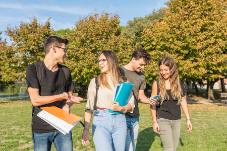 Happy students at park carrying books and having fun - Small group of teenage best friends together at park after school - Sunny summer day in Italy Zdjęcie Seryjne