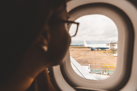 Woman looking out of airplane window at the airport - Aircraft on the tarmac at the airport and woman looking at it - Travel concept with a romantic or nostalgic mood