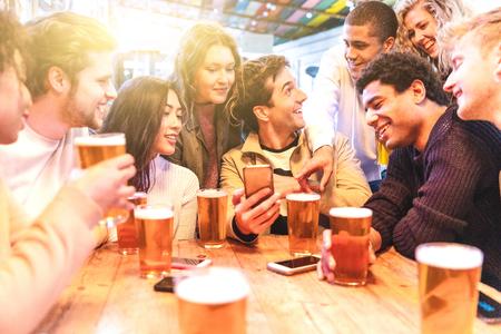 Fröhliche tausendjährige Freunde in der Kneipe, die Bier trinken - Gruppe gemischtrassiger Menschen, die zusammen Spaß in der Kneipe haben und auf das Smartphone schauen - Geburtstagsfeier oder After-Work-Meeting, Glück und Teamwork-Konzepte