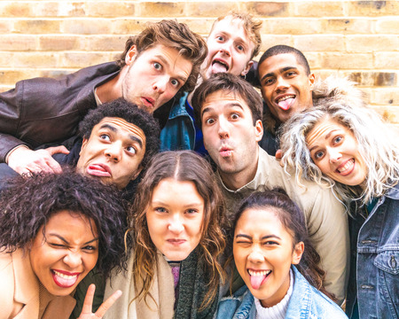 Multiracial friends taking selfie and making funny faces - Group of millennials men and women together in London having fun and enjoying time together - Friendship and millenial lifestyle concepts Stock Photo