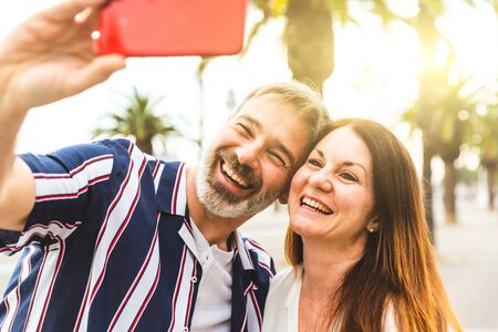 Happy adult couple taking a selfie in Barcelona at sunset - Man and woman together on a summer sunny day in Barcelona, taking a selfie with palm trees and sun on background - Love and lifestyle concepts