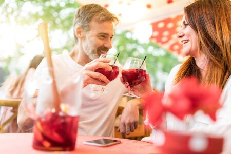 Happy couple dating and having a drink in Barcelona - Adult man and woman together at a bar in Barcelona enjoying a glass of sangria and having a gun conversation - Love and lifestyle concepts