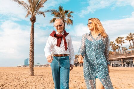 Senior couple walking on the beach in Barcelona - Adult woman and man bonding and enjoying time together on a summer day in Spain - Summer and travel concepts at seaside in Barcelona