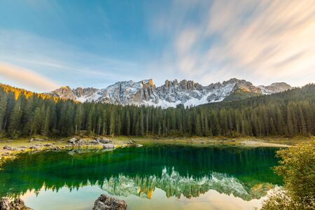 Lake Carezza or Karersee at sunset, wide angle view of scenic landscape in Italy. Dolomites mountains on background, Italian Alps. Nature and travel concepts, long exposure photo