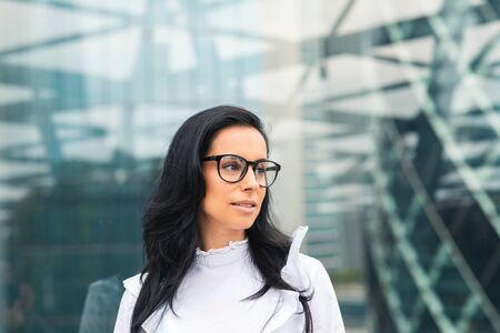 Business woman portrait with modern blurred background. Beautiful caucasian woman wearing eyeglasses and white shirt looking away from camera. Young beautiful woman in the financial district