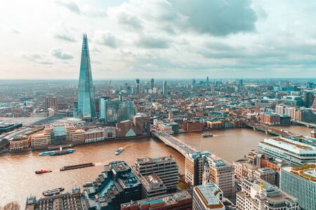London aerial view with modern buildings and skyscraper, Thames river and clouds in the sky - Architecture and travel photo, teal and orange vintage filter applied - Beautiful London panoramic view Reklamní fotografie - 128939515