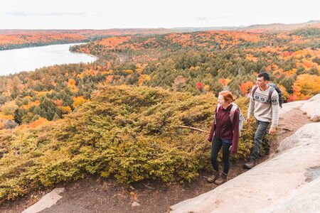 Couple hiking, autumn scene, colourful trees on background - Two young hikers on a path between rocks with colourful trees all around - Wanderlust feeling, hiking and nature concepts. Zdjęcie Seryjne