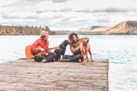 Happy young couple playing with their dog on a dock - Man holding a guitar, both wearing a rain jacket and cuddling dogs - Love and nature concepts