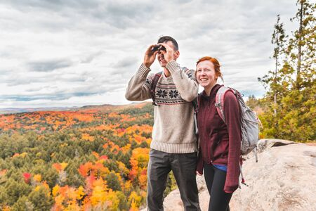 Couple looking at panorama with a binocular from the top of the rocks - Two young hikers staring at the beautiful view below them with colourful trees all around - Wanderlust feeling, hiking and nature concepts. Zdjęcie Seryjne