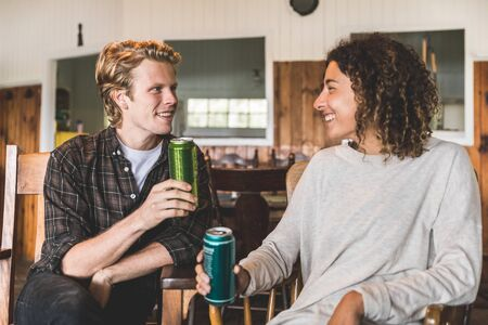 Happy couple enjoying a drink in a wood cabin in Canada - Blond man and curly woman looking each other and smiling, both holding a can of beer - Love and relax concepts. Zdjęcie Seryjne