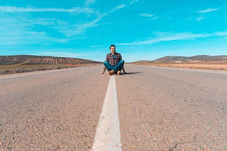Man sitting in the middle of a empty straight road - Travel concept, road running in the countryside through a remote desert area in Spain - Wanderlust and adventure Zdjęcie Seryjne