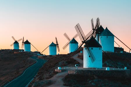 Windmills silhouette in Consuegra, Spain, at sunrise - Beautiful view of old windmills in the Castilla La Mancha region, Spanish countryside - Travel and architecture concept, teal and orange filter