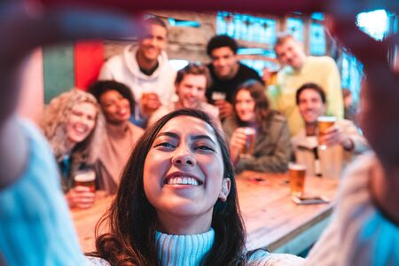 Happy friends taking a group selfie at pub - Group of multiracial millennial people having fun together at pub and taking a photo - Birthday party or after work meeting, happiness and teamwork concepts