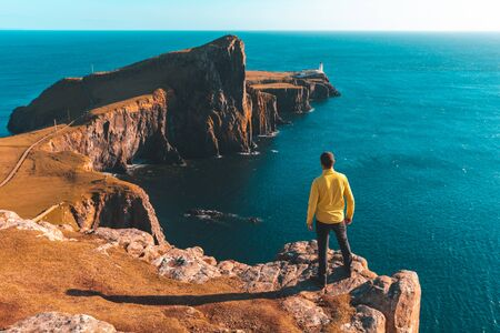 Man standing on top of a cliff in Scotland - Hiker looking at the beautiful view of a rocky coast in the Isle of Skye on a sunny autumn day - Filter applied, travel and adventure concepts Zdjęcie Seryjne