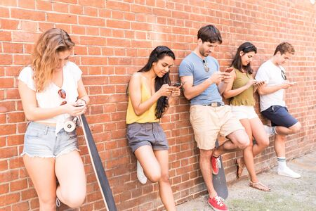 Group of friends using smartphone not interested in each other. Five persons leaning to a wall and looking at their own phone, ignoring friends. Technology and social media addiction in real life.