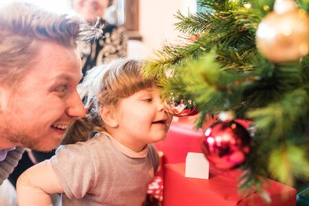 Baby girl and dad playing with Christmas tree decorations at home. Playful festive situation with blonde funny girl looking at herself on the ball. Christmas and holidays concepts