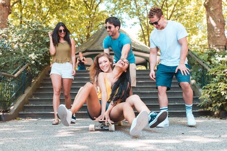 Group of friends having fun with skateboard at park. Multi ethnic people enjoying time together and playing in London. Carefree and lifestyle concepts with real people Zdjęcie Seryjne