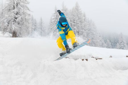 Man with snowboard jumping and doing tricks on the snow - Winter sport scene with a young man enjoying snow ride off piste - Sport and winter concepts