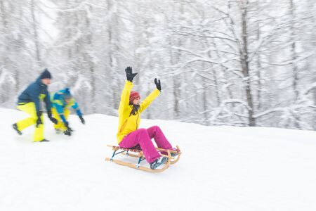 Friends having fun on the snow sliding with a little sled - Girl being pushed by two boys on a sledge - Blurred panning shot from the side with white wood on background Zdjęcie Seryjne