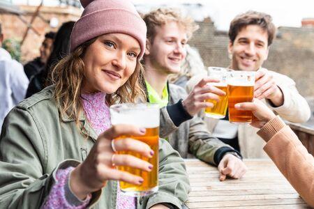 Amigos bebiendo y brindando con cerveza en la cervecería de pub - Hermosa mujer joven mirando a la cámara y levantando su vaso de pinta - Conceptos de estilo de vida y bebida en Londres