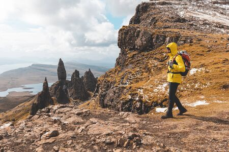 Man hiking in Scotland, Isle of Skye at the Old Man of Storr - Hiker looking at the beautiful panorama with the famous rocks of the Isle of Skye on a autumn or winter day - Filter applied, travel and adventure concepts