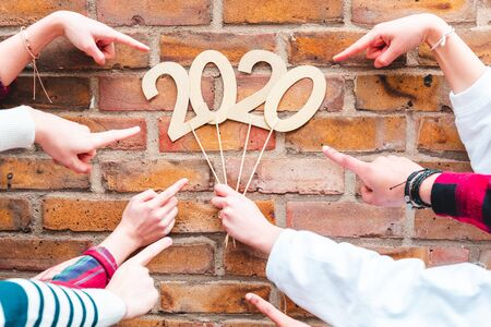 Fingers pointing to new year 2020 sign - Teen friends holding a 2020 sign and celebrating new year - Holidays and culture concepts