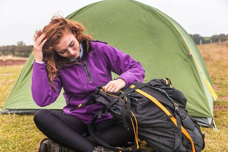 Young woman camping on a cloudy day in Cornwall- Red hair woman with a tent on background looking into her backpack - Nature and adventure concepts
