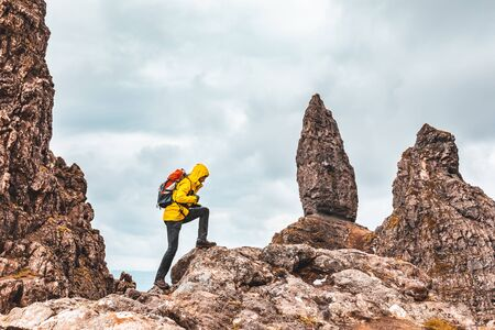 Man hiking in Scotland, Isle of Skye at the Old Man of Storr - Hiker climbing on rocks with the famous rock of the Isle of Skye on a cloudy  day - Filter applied, travel and adventure concepts