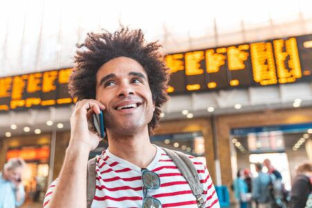Happy man on the phone at train station in London - Mixed race young man with curly hair smiling and talking on the phone, waiting for train - Backpacker travel and lifestyle