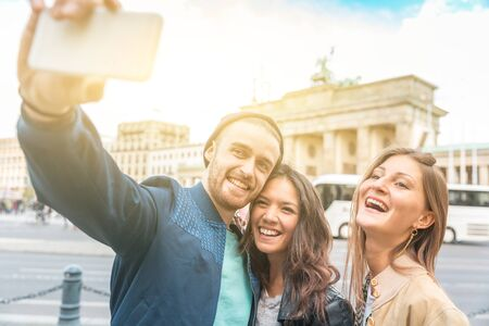 Multiracial group of friends taking a selfie in Berlin - Two women and a man looking at phone camera with Brandenburg Gate on background - Lifestyle, friendship and tourism concepts Imagens