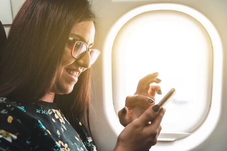 Woman travelling by airplane typing on her smartphone - Beautiful and smiling happy young woman texting with her mobile phone while on a trip - travel and technology concepts 版權商用圖片