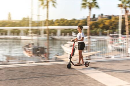 Happy woman riding e-scooter in Malaga - young woman enjoying a ride on electric scooter at seaside with boats and palm trees on background - lifestyle and travel concepts Imagens