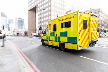 Emergency ambulance rushing on the street with emergency lights flashing in London city centre - first aid responder at work going to the hospital - emergency, health and medical concepts