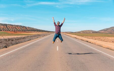 Happy successful man jumping in countryside road - Young man wearing checked shirt triumph a victory with a jump and raising arm - Happiness and success concepts, taken in Spain