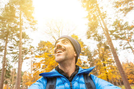 Happy man taking a selfie in the wood with beautiful autumn vibes - Young man alone enjoying time in a remote forest away from city and busy life - lifestyle and nature