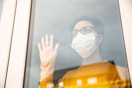 Woman wearing a face mask isolating at home and looking out of the window - Young woman feeling sad alone at home due to coronavirus quarantine and lockdown Stock Photo