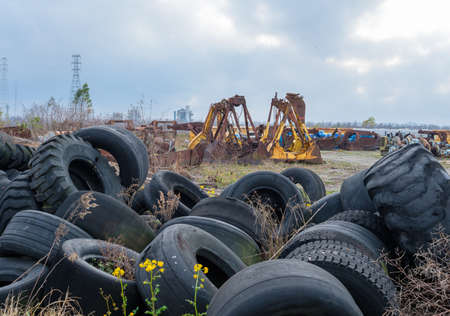 Industrial graveyard with discarded large tires and heavy equipment attachments along the river